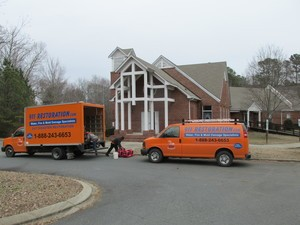 Water Damage Restoration Van And Truck Parked At ResidentialJob Site